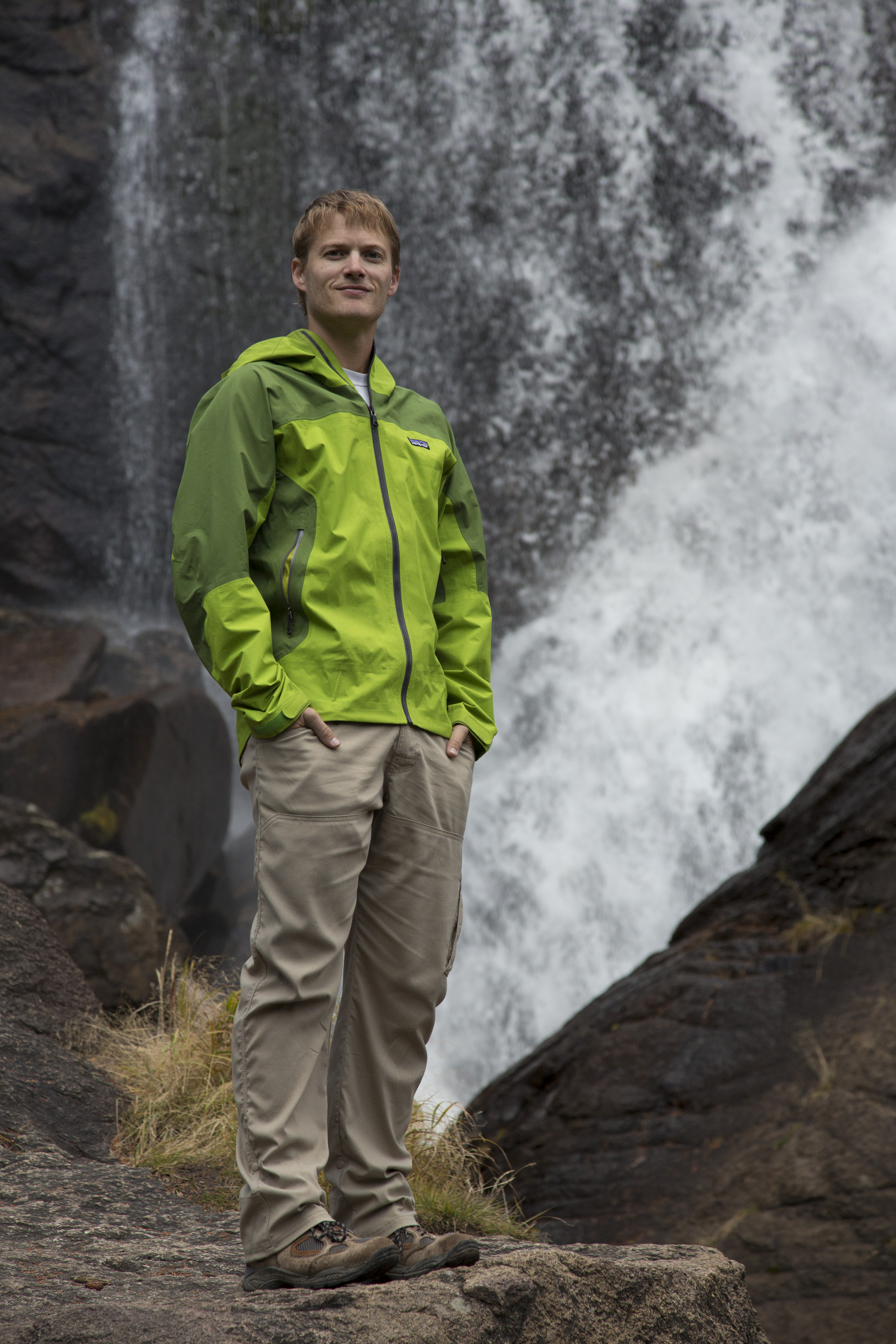 Wearing a green jacket, Chris Lawrence, the founder of Hope Has Arrived and cancer survivor, stands in front of a waterfall in Rocky Mountain National Park